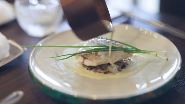 pouring cream sauce on fish in french restaurant - french food stock videos & royalty-free footage