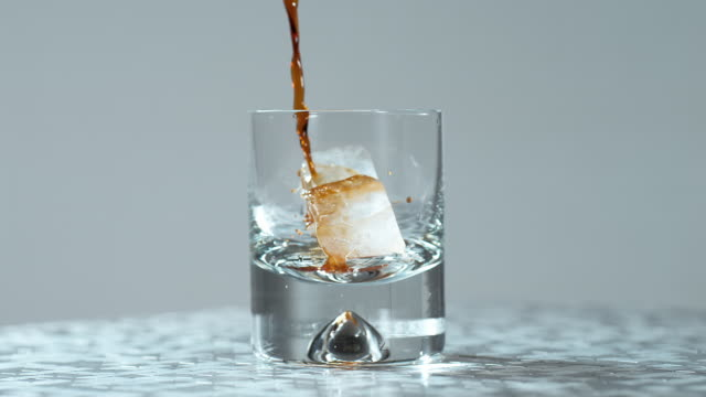 pouring dark liquid in a glass with ice cubes / slow motion