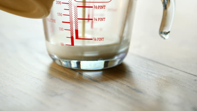 pouring double cream into measuring jug - instrument of measurement stock videos & royalty-free footage