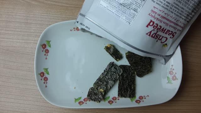 gießen getrocknete laminaria algen snack in einem teller - kelp stock-videos und b-roll-filmmaterial
