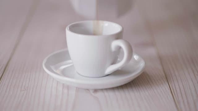 vídeos de stock, filmes e b-roll de derramando o café fresco no copo para prestar serviços de manutenção - xícara de café