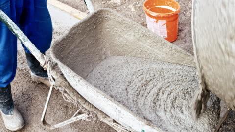 time-lapse pouring fresh concrete from the mixer into a wheelbarrow - concrete stock videos & royalty-free footage