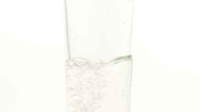 vídeos de stock e filmes b-roll de pouring glass of water - gota a cair na água