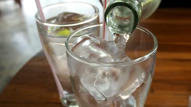 vídeos de stock, filmes e b-roll de um copo de água vertendo - gelo