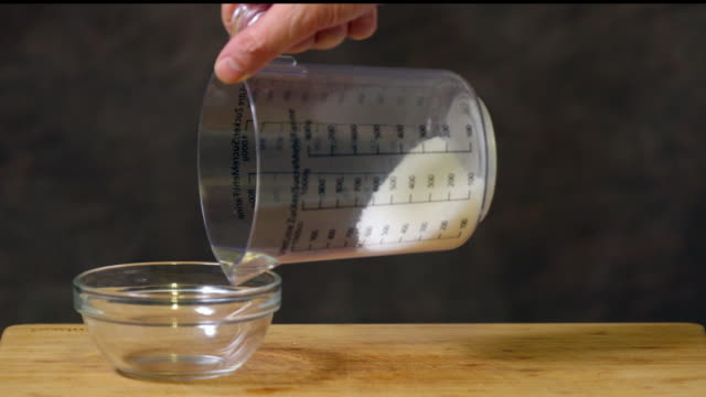 Pouring granulated sugar in glass bowl.