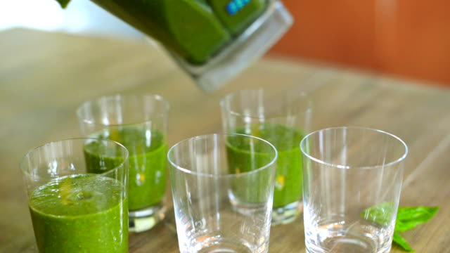 Pouring green smoothies in glasses