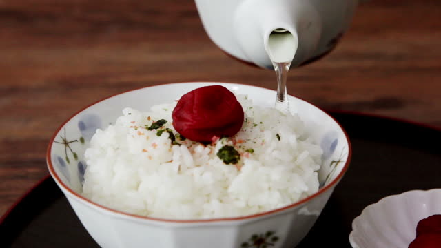 Pouring green tea inside the rice bowl (Ochazuke rice in seasoned tea water with umeboshi Japanese apricot (Japaneses traditional food)