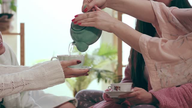 pouring her friends tea while relaxing on bed - slumber party stock videos & royalty-free footage