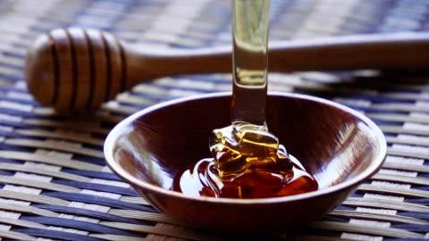 vídeos y material grabado en eventos de stock de verter la miel en una taza de madera lenta - miel