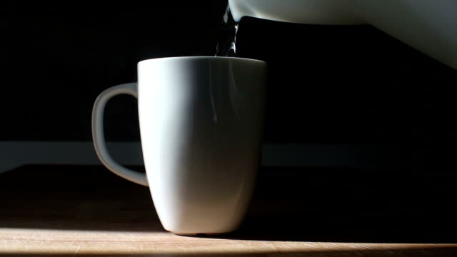 pouring hot boiling water from kettle in to a white coffee or tea cup - overflowing stock videos & royalty-free footage