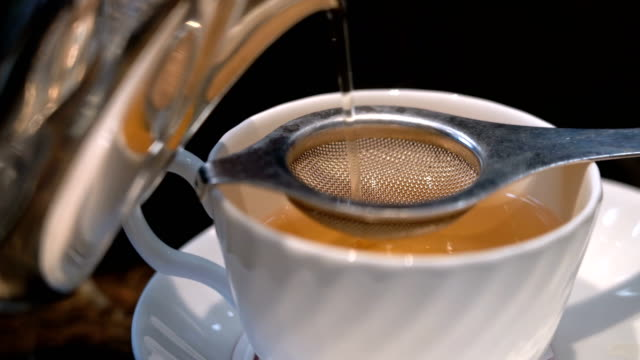 4k pouring hot tea to tea strainer - teapot stock videos & royalty-free footage