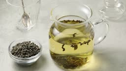 Pouring hot water in a glass teapot to make green gunpowder tea