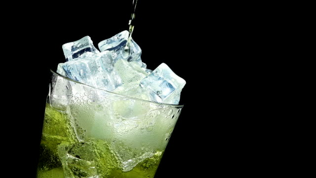 pouring inka kola soda into a glass of ice at slow motion on a black background - soda stock videos and b-roll footage