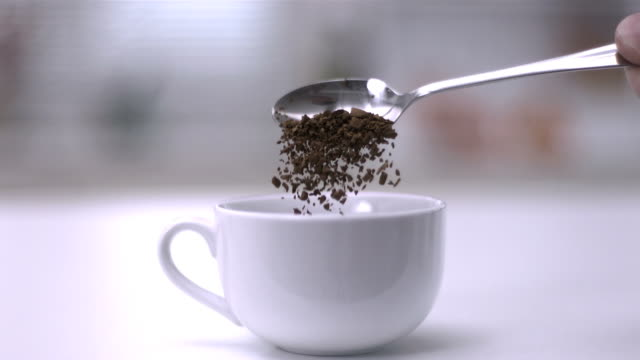 pouring instant coffee off teaspoon into a white cup - teaspoon stock videos and b-roll footage