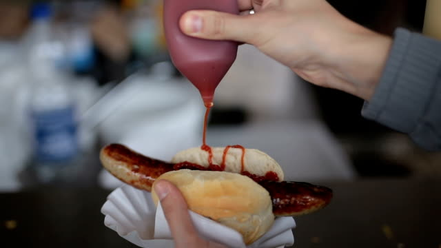 pouring ketchup over the sausage/hotdog - sausage stock videos & royalty-free footage