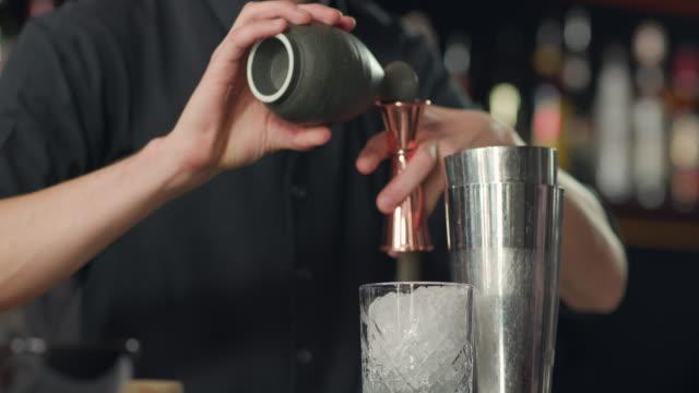 vidéos et rushes de verser la liqueur dans le jigger de la cruche - shaker