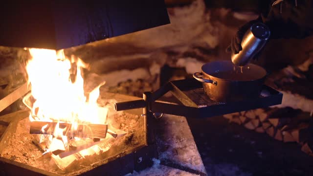 pouring liquid into a pot over an outdoor fireplace, in lapland, finland - cold temperature stock videos & royalty-free footage