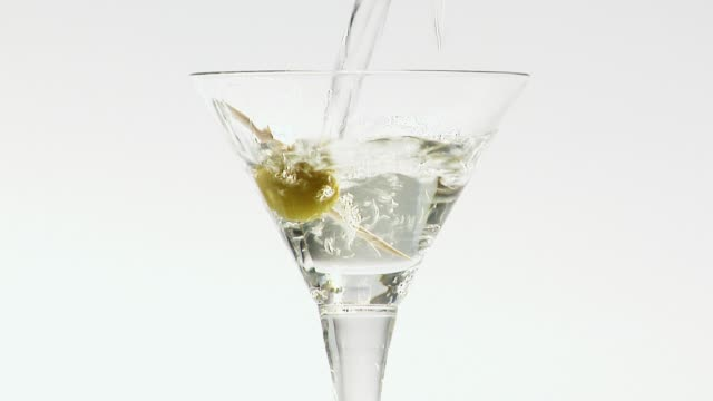 pouring martini into a glass with an olive - martini stock videos & royalty-free footage