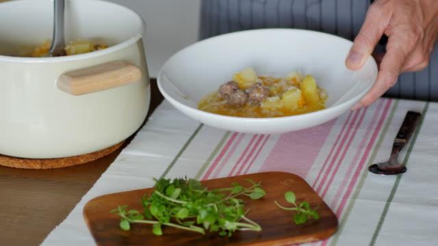 vidéos et rushes de pouring meatball soup from white enamel pan into a bowl - bol à soupe