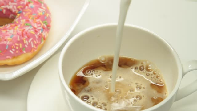pouring milk in a coffee cup and strawberry donut - doughnut stock videos & royalty-free footage