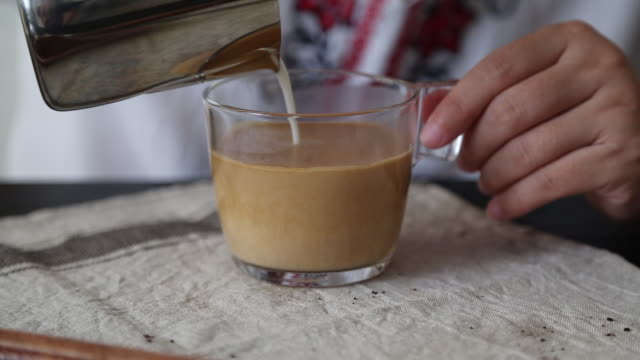 stockvideo's en b-roll-footage met pouring milk in coffee to make latte - zuivelproduct