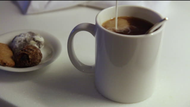 Pouring milk into black coffee to be served with desserts