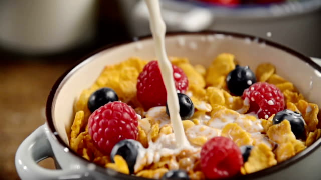 Pouring Milk into Bowl with Cornflakes
