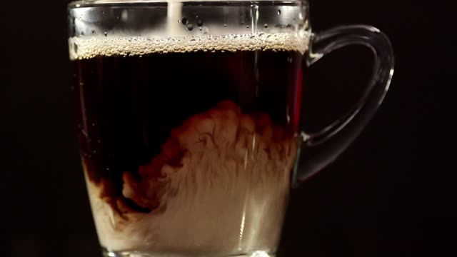 Pouring Milk into Cup of Coffee