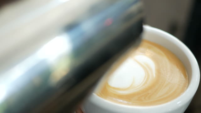 Pouring milk into cup of hot coffee , make latte art