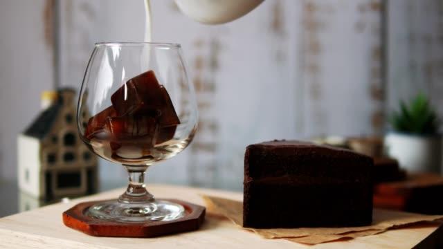 stockvideo's en b-roll-footage met gieten van melk in glas met ijsblokjes - koffie drank