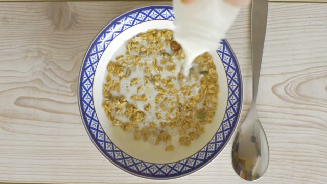 pouring milk into  granola bowl - bowl stock videos and b-roll footage