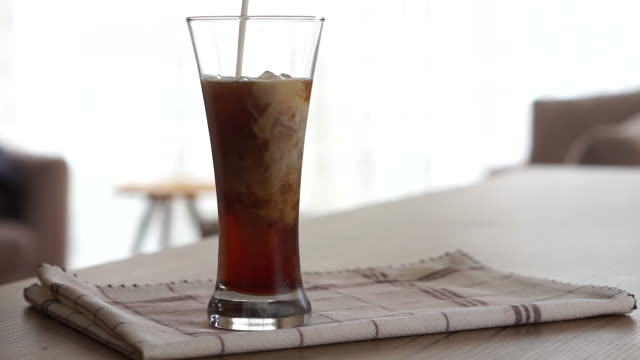 Pouring Milk Into Iced Coffee