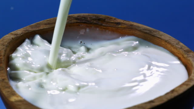 pouring milk into wooden bowl - blue background stock videos & royalty-free footage