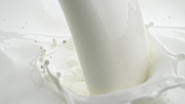pouring milk. splash crown. - milk stock videos & royalty-free footage