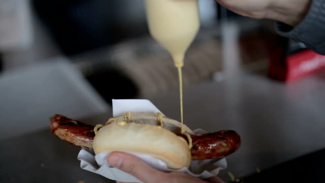 vídeos de stock e filmes b-roll de pouring mustard over the sausage , best street food in germany - estilo de vida pouco saudável