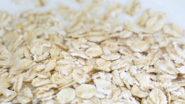 pouring oat flakes close up. - oatmeal stock videos & royalty-free footage