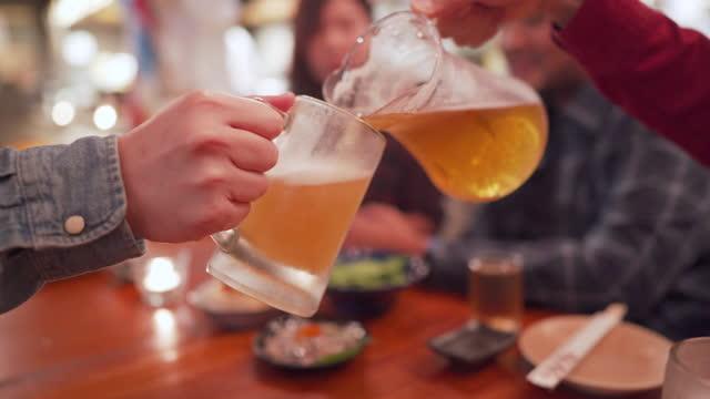 日本のカフェで友人のためのマグカップにビールを注ぐ - 居酒屋点の映像素材/bロール