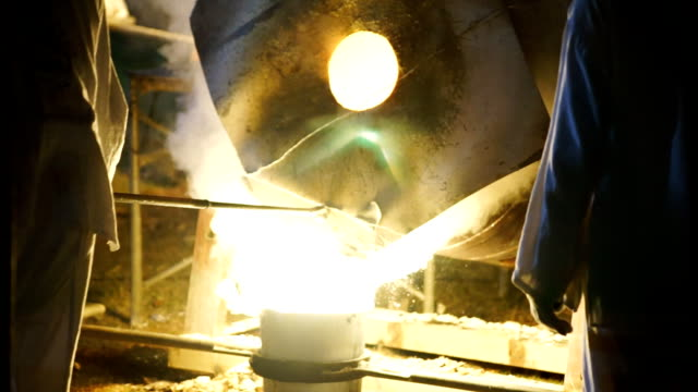 slo mo pouring of liquid metal in castings while layered white smoke from blast furnaces. processing steel in iron foundry plant. - metal clip stock videos and b-roll footage