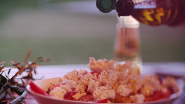 pouring olive oil on a large greek salad in outside sunny holiday setting - salad oil stock videos & royalty-free footage