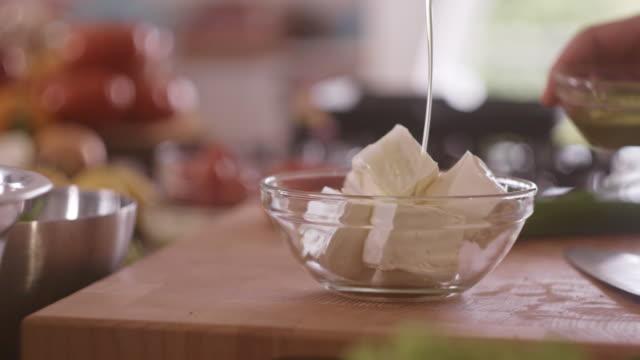 フェタ ・ チーズをオリーブ オイルを注ぐ - シェーブルチーズ点の映像素材/bロール