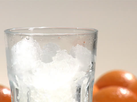 pouring orange juice into a cold glass with crushed ice, close up - crushed ice stock videos & royalty-free footage
