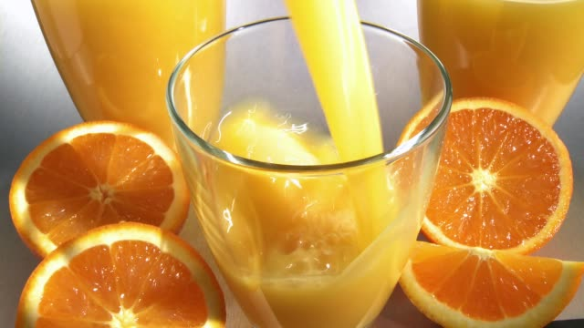 vídeos y material grabado en eventos de stock de pouring orange juice into a glass - zumo de naranja