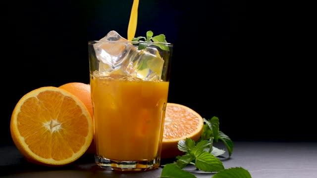 orangensaft gießen in glas - slow-motion - orangensaft stock-videos und b-roll-filmmaterial