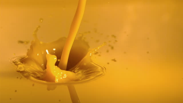 cu slo mo pouring orange juice into pool of orange juice / new jersey, usa - orangensaft stock-videos und b-roll-filmmaterial