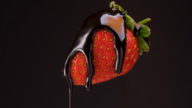 pouring out chocolate sauce on a fresh strawberry - strawberry stock videos & royalty-free footage