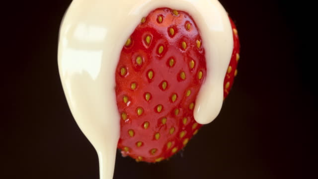 pouring out white chocolate sauce on a fresh strawberry - condensed milk stock videos & royalty-free footage
