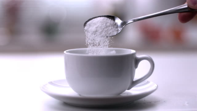 Pouring powdered sugar from teaspoon into a white cup