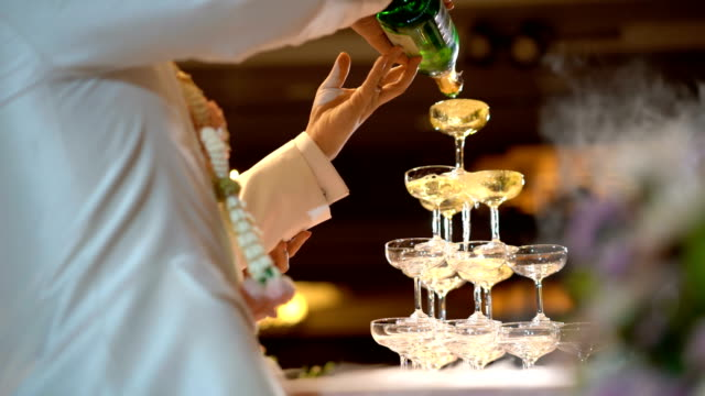 4k pouring pyramid champagne glasses in wedding ceremony - tower stock videos & royalty-free footage