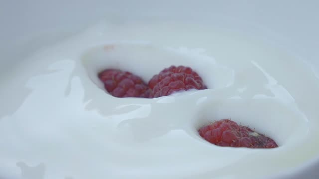 pouring raspberry on yogurt slow motion. - yoghurt stock videos and b-roll footage
