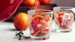 Pouring red orange juice in a large glass or blood orange sparkling vodka cocktail or aperitif with campari